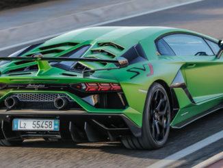 Ein grüner Lamborghini Aventador SVJ Coupé fährt auf einer Rennstrecke.