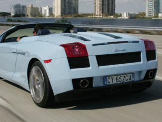 Ein hellblauer Lamborghini Gallardo Spyder fährt auf einer Uferpromenade an einigen Hochhäusern vorbei.