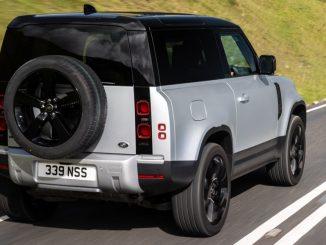 Ein silberner Land Rover Defender fährt 2021 auf einer britischen Landstraße.