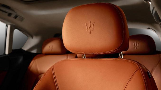 Nahaufnahme von der Kopfstütze des Fahrersitzes eines Maserati Levante mit dem eingraviertenEmblem