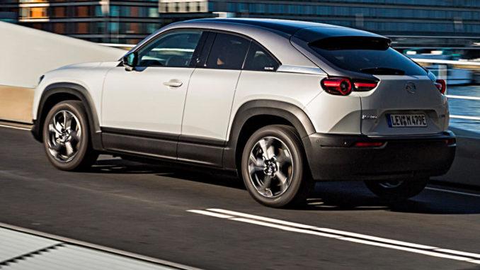 Mazda MX-30, 2020, Mondsteinweiß Metallic, Fahraufnahme über eine Brücke.