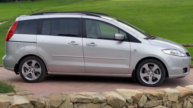 Ein silberner Mazda5 steht 2005 neben einem Golfplatz.