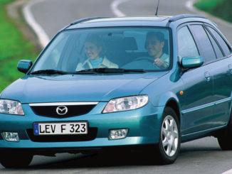 Ein türkisener Mazda 323 fährt 2000 auf einer Landstraße
