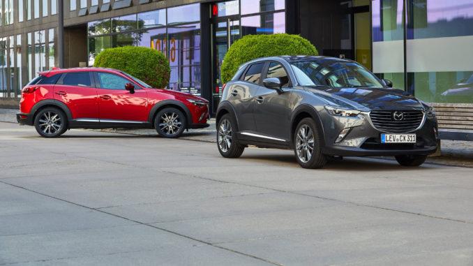 Ein roter und ein grauer Mazda CX-3 stehen 2017 vor einem Bürogebäude.
