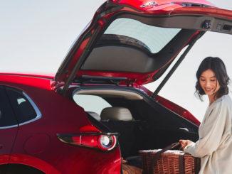 Die Fahrerin eines roten Mazda CX-30 lädt 2020 den Kofferraum aus.