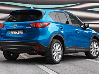 Ein blauer Mazda CX-5 steht 2012 auf einem Parkplatz vor einer bunten Plane.