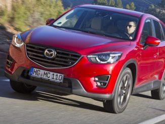 Ein roter Mazda CX-5 fährt 2015 auf einer Landstraße.