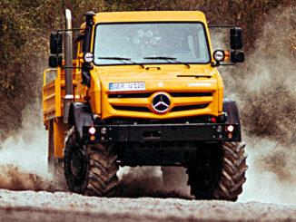 Ein orangener Mercedes Unimog fährt in einer Kiesgrube um die Kurve.
