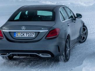 Mercedes-Benz C 300 d 4MATIC (BR205), designo selenitgrau magno, designo Leder platinweiß pearl/schwarz fährt auf einer verschneiten Passstraße.