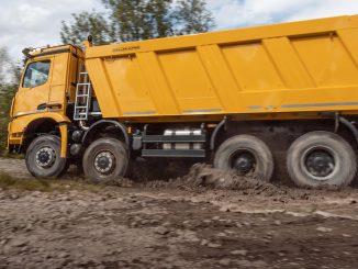 Ein orangener Arocs 4151 AK, 8x8/4, OM 471, R6, 12,8 l, Euro VI, D, 375 kW (510 PS), 2500 Nm, fährt 2020 durch den Schlamm.