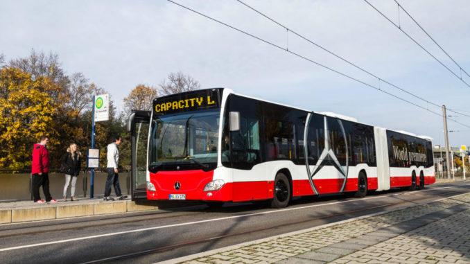 Ein rot-weißer Evobus Mercedes Capacity L steht 2014 an einer Haltestelle und lässt Fahrgäste vorne zusteigen