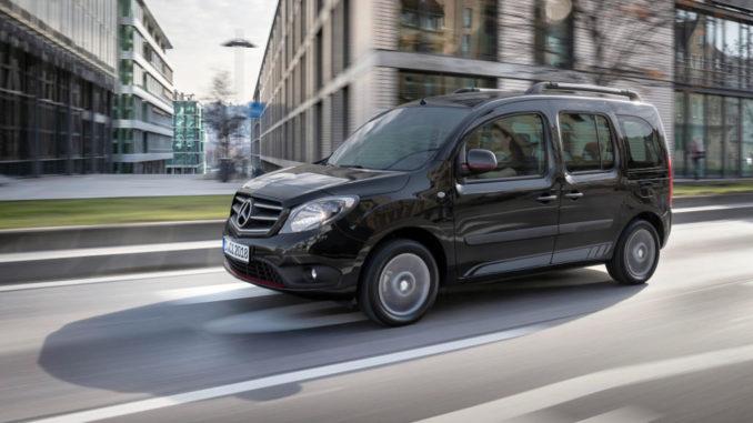 Ein schwarzer Mercedes-Benz Citan Tourer fährt 2019 an einem Bürogebäude vorbei.