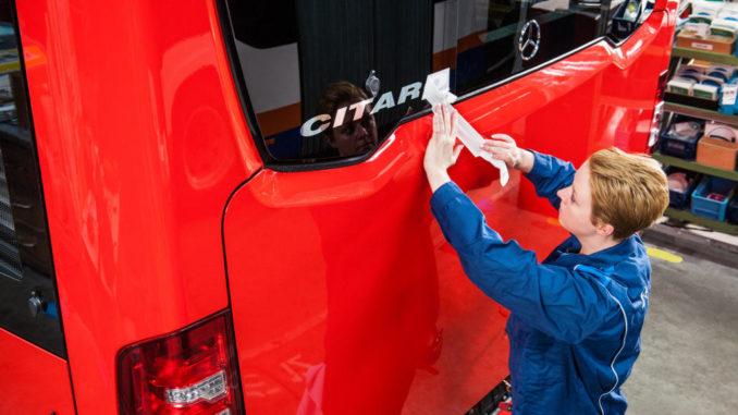 """Das EvoBus Werk Mannheim ist mit knapp 3.500 Beschäftigten einer der größten Arbeitgeber in der Region. In der Montage bringt eine Mitarbeiterin den Schriftzug """"Citaro"""" auf den Omnibus auf."""