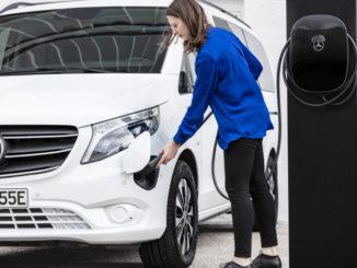 Ein weißer Mercedes eVito wird von seiner Besitzerin an die Ladebox angeschlossen.