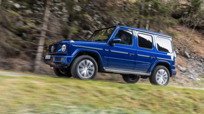 Ein Mercedes G 350 d; brilliantblau metallic, designo Leder Nappa espressobraun / schwarz, fährt im Dezember 2018 einen Waldweg bergauf.