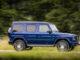 Ein Mercedes-Benz G 400 d; brilliant blau; Leder Nappa macchiatobeige/yachtblau, fährt 2019 auf einem Waldweg.