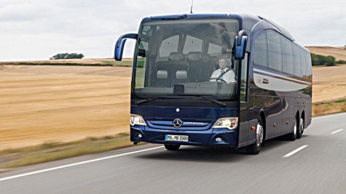 Ein blauer Mercedes Travego der Daimler-Tochter Evobus fährt an einem Weizenfeld vorbei.