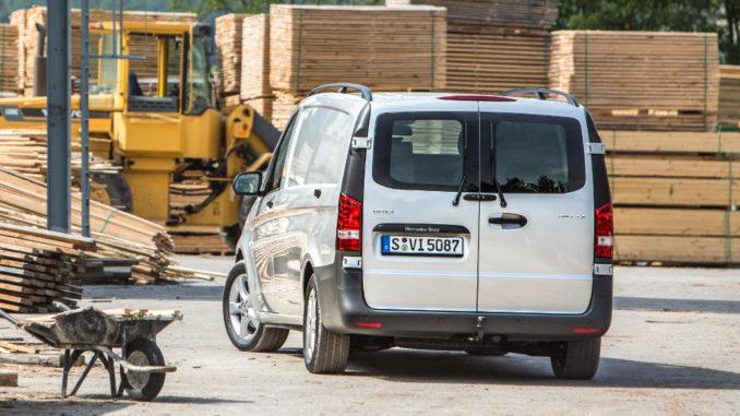 Ein silberner Mercedes Vito 116 CDI steht vor einem Holzstapel.