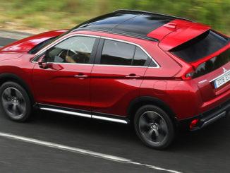 Ein roter Mitsubishi Eclipse Cross fährt auf einer Landtsraße.