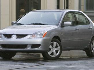 EIn silberner 2004 Mitsubishi Lancer LS steht in den USA vor einem Bürogebäude auf regennasser Straße.