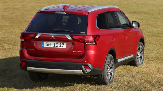 Ein roter Mitsubishi Outlander steht 2017 auf einer Wiese.