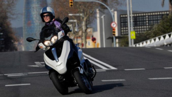 Frau legt sich nach Überquerung einer Brück mit ihrer Piaggio MP3 Yourban in die Kurve.