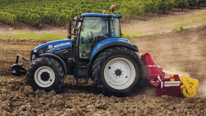 Ein blauer New Holland T5_115_ElectroCommand plügt einen Acker.