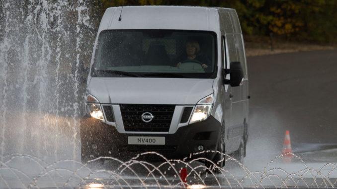 Ein silberner Nissan NV400 fährt bei einem Fahrsicherheitstraining über eine bewässerte Straße.