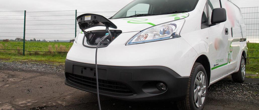 Ein weißer Nissan e-NV200 wird 2020 auf einem Betriebsgelände geladen.
