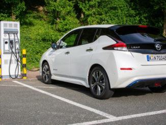 Ein weißer Nissan Leaf steht 2019 an einer öffentlichen Ladesäule für Elektroautos.