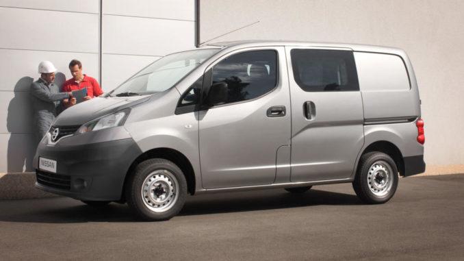 Ein grauer Nissan NV200 steht mit zwei Handwerkern auf einem Betriebshof.