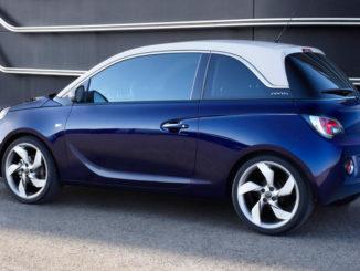 Ein blauer Opel Adam Jam steht vor einem Bürogebäude.