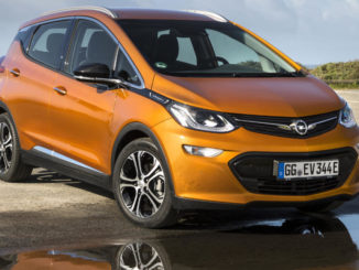 Ein rostfarbener Opel Ampera-e spiegelt sich in einer Pfütze.