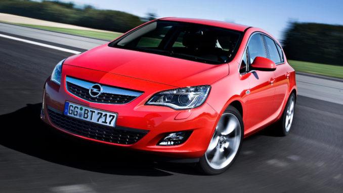 Ein roter Opel Astra J wendet 2010 auf einer Straße.