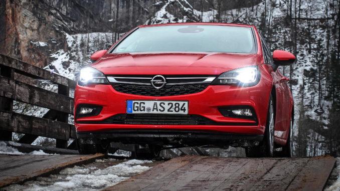 Ein roter Opel Astra K mit IntelliLux LED-Licht steht vor einer Felswand auf einer Holzbrücke.