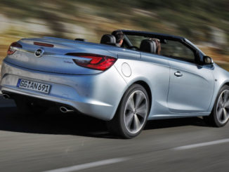 EIn silberner Opel Cascada fährt mit hoher Geschwindigkeit auf einer Landstraße.