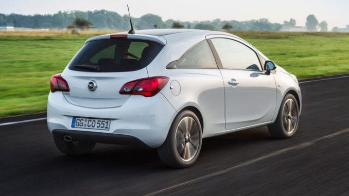 Ein weißer Opel Corsa E fährt in der Morgendämmerung über eine Landstraße.