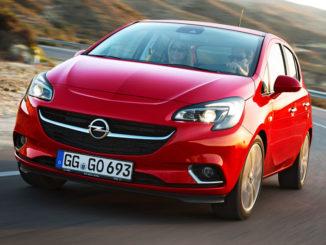 Ein roter Opel Corsa E fährt auf einer Landstraße durch eine mediterrane Landschaft.
