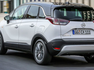 Ein weißer Opel Crossland X fährt durch die Straßen einer Stadt.