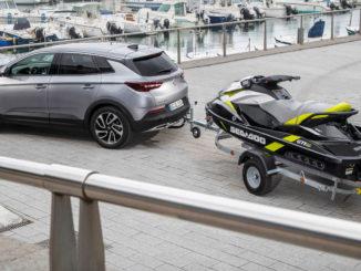 Ein silberner Opel Grandland X steht 2019 in einem Hafen mit einem Jetski auf dem Anhänger.
