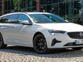 Ein weißer Opel Insignia Sports Tourer steht 2020 vor einer Glasfassade.