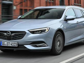 Ein hellblauer Opel Insignia B Sportstourer fährt an einem Backsteingebäude vorbei.