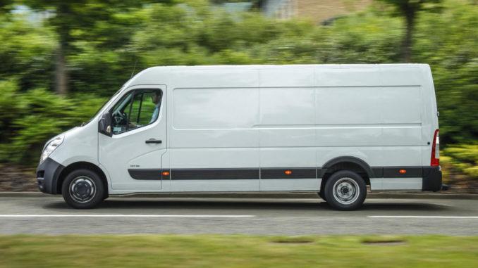 Ein weißer Opel Movano fährt an einer Hecke vorbei.