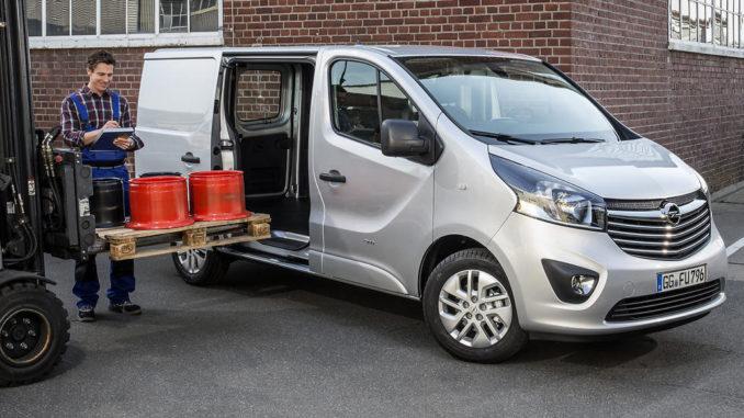 Ein silberner Opel Vivaro B Panel Van wird von einem Gabelstapler mit einer Palette beladen.