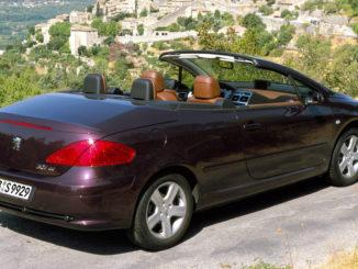 Ein lilafarbener Peugeot 307CC steht vor dem Panorama eines Bergdorfes.