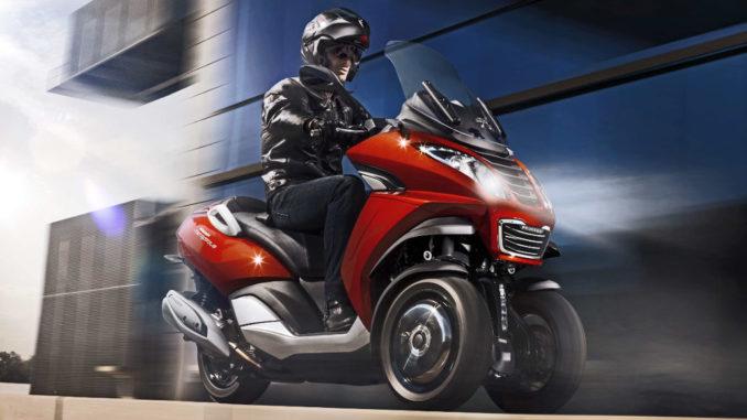 Ein roter Peugeot Scooter vom Typ Metropolis fährt 2014 durch eine dunkle Stadt.