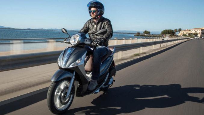 Ein Mann fährt mit einer grauen Piaggio Medley 125 auf einer Küstenstraße.