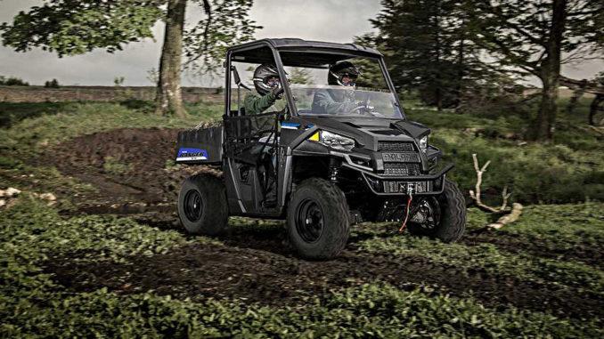 Ein Polaris Ranger EV fährt mit zwei Personen durchs Gelände.