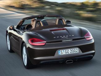 Ein brauner Porsche Boxster fährt durch eine karge Lndschaft.
