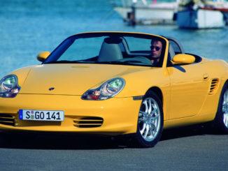 Ein gelber Porsche Boxster (986) steht vor einem Hafenbecken.